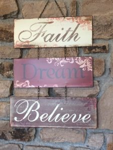 sign with the words faith, dream, believe - words that encourage me on my writing journey