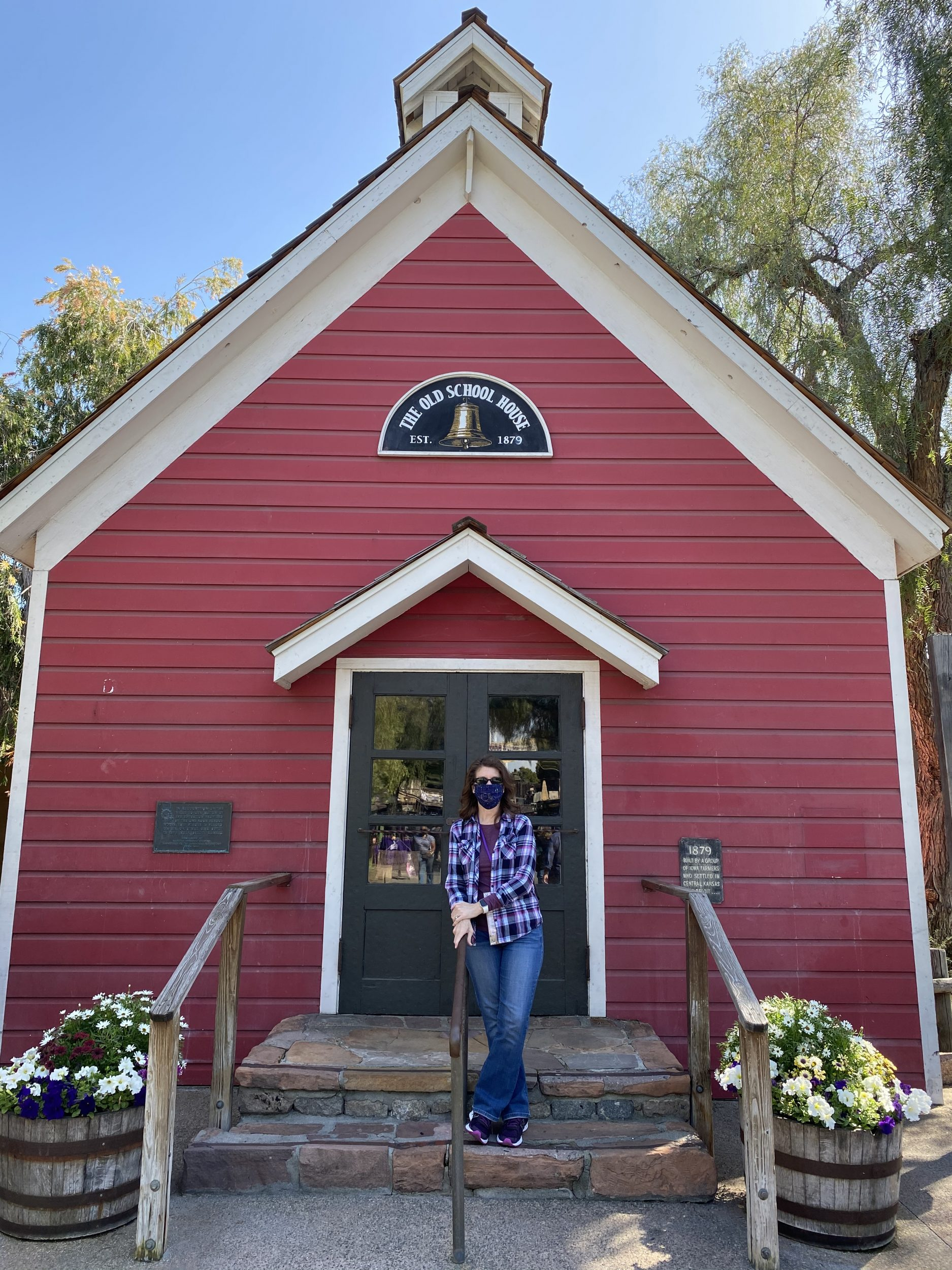 Denise M. Colby standing in front of historical red one-room schoolhouse at Knotts Berry Farm